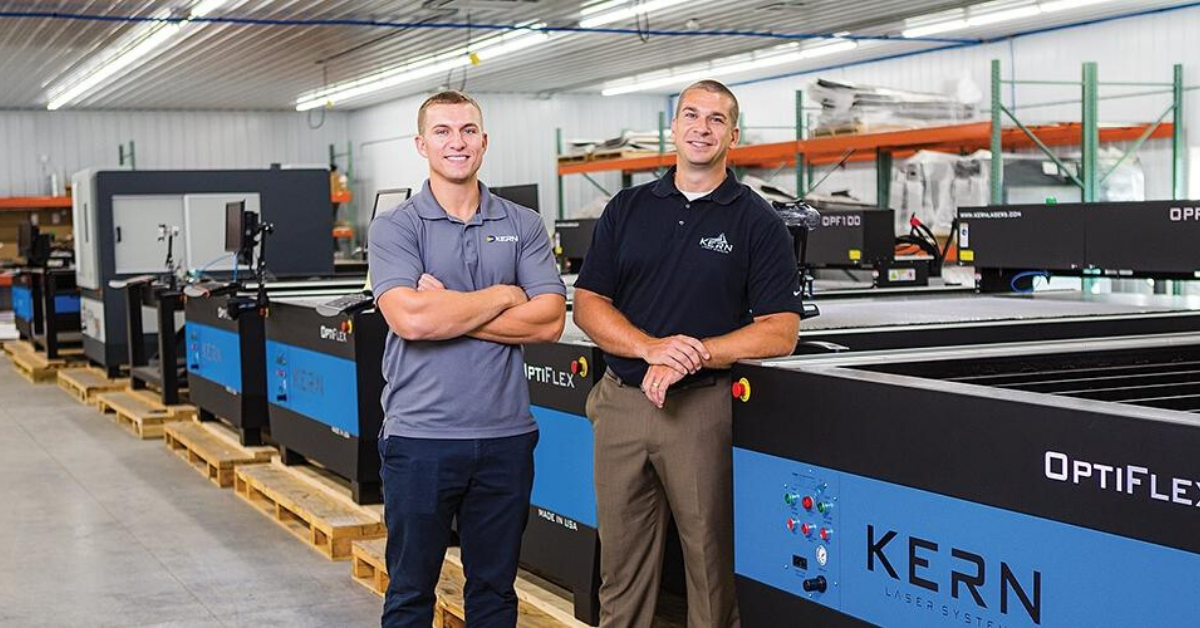 Kern employees proudly standing in front of laser equipment